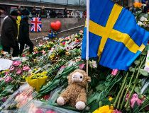 People gather at a makeshift memorial to commemorate the victims of last Friday's terror attack near the site where a truck drove into Ahlens department store in Stockholm, on April 14, 2017. Four people died and fifteen were injured when a truck plunged