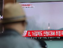 A man watches a TV news program reporting about North Korea's missile firing