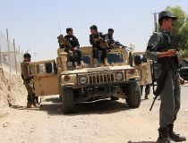 Afghan security personnel sit on atop an armoured vehicles