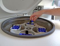 Scientist putting test tube into centrifuge, embryologist