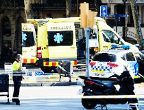 A policemen and a medical staff member stand past police cars and an ambulance in a cordoned off area after a van ploughed into the crowd, injuring several persons on the Rambla in Barcelona on August 17, 2017. / AFP PHOTO / Josep LAGOJOSEP LAGO/AFP/Getty