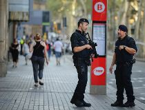 Armed police officers patrol a street in Las Rambla