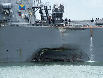 Damage to the portside is visible as the Guided-missile destroyer USS John S. McCain (DDG 56) steers towards Changi naval base in Singapore following a collision with the merchant vessel Alnic MC Monday, Aug. 21, 2017. The USS John S. McCain was docked at