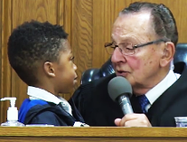 In this Aug. 10, 2017 photo, Providence Municipal Court Judge Frank Caprio sits on the bench in Providence, Rhode Island. The 80-year-old judge has been winning hearts and clicks on Facebook with a mix of compassion and humor from his courtroom in Provide