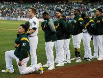 Oakland Athletics catcher Bruce Maxwell kneels