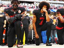 (L-R) Eli Harold #58, Colin Kaepernick #7, and Eric Reid #35 of the San Francisco 49ers kneel in protest during the national anthem prior to their NFL game against the Arizona Cardinals at Levi's Stadium on October 6, 2016 in Santa Clara, California. (Pho