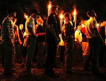 In this photo taken Friday, Aug. 11, 2017, multiple white nationalist groups march with torches through the UVA campus in Charlottesville, Va. Hundreds of people chanted, threw punches, hurled water bottles and unleashed chemical sprays on each other Satu