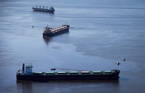 Spill response boats work to contain bunker fuel leaking from the bulk carrier cargo ship Marathassa, second from top, anchored on Burrard Inlet in Vancouver, B.C., on Thursday April 9, 2015. THE CANADIAN PRESS/Darryl Dyck