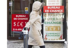 A woman walks past a currency exchange store Wednesday, January 20, 2016 in Montreal. The Canadian dollar came close to falling below 68 cents US in overnight trading amid further pressure on oil prices and uncertainty about what the Bank of Canada will do in response to weakened economic conditions.THE CANADIAN PRESS/Ryan Remiorz