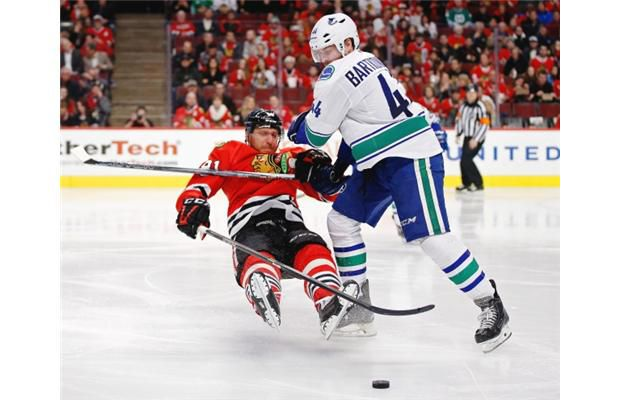 Chicago Blackhawks right wing Marian Hossa (81) and Vancouver Canucks defenseman Matt Bartkowski (44) collide during the second period of an NHL hockey game in Chicago, Sunday, Dec. 13, 2015.