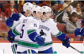 Vancouver Canucks' Jared McCann, right, celebrates his goal against the Arizona Coyotes with Derek Dorsett (15) and Adam Cracknell, left, during the first period of an NHL hockey game Friday, Oct. 30, 2015, in Glendale, Ariz.