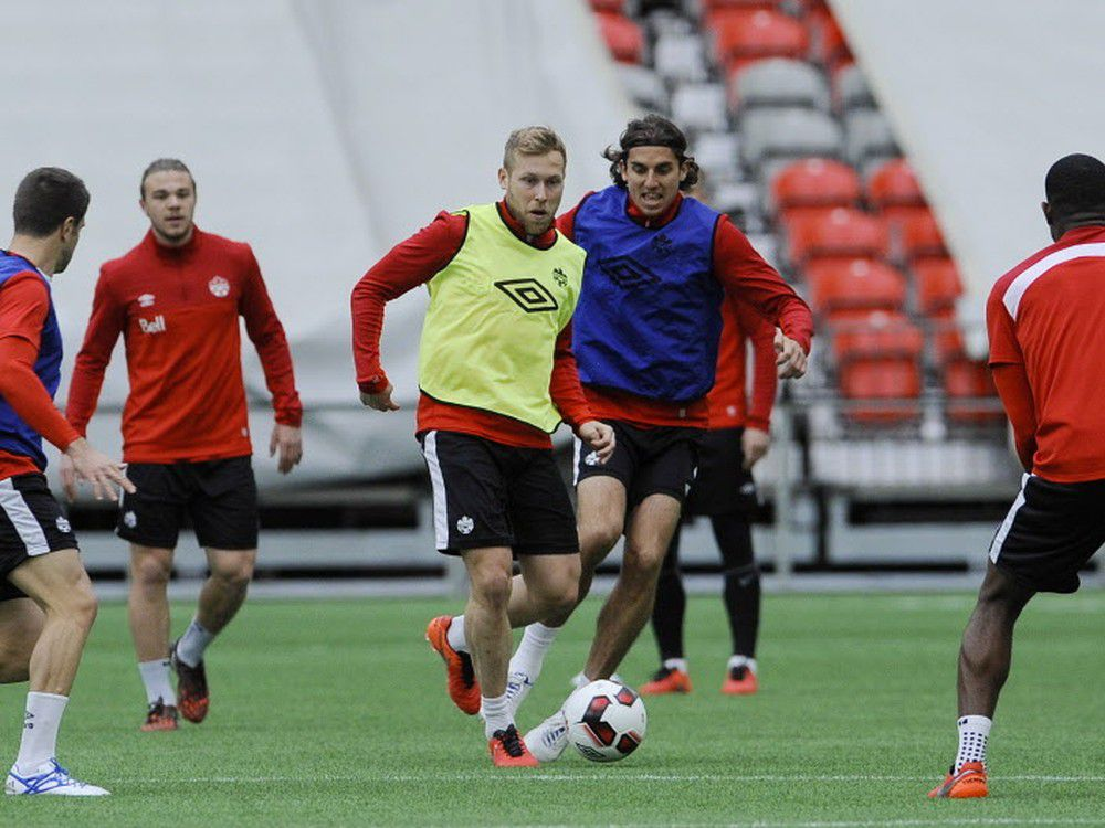 Scott Arfield (centre, in yellow bib) takes control of the ball during a Canada practice session on Tuesday in Vancouver.