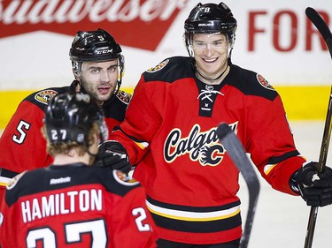 Calgary Flames' Joe Colborne, right, celebrates his goal with teammates Dougie Hamilton, left, and Mark Giordano during second period NHL hockey action against the Vancouver Canucks in Calgary, Thursday, April 7, 2016.THE CANADIAN PRESS/Jeff McIntosh