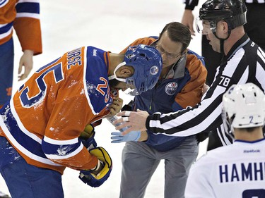 Edmonton Oilers' Darnell Nurse (25) receives treatment after being injured against the Vancouver Canucks during first period NHL action in Edmonton, Alta., on Wednesday April 6, 2016. THE CANADIAN PRESS/Jason Franson