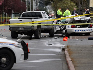 Investigators examine the scene of the crash involving a police car and a pickup truck in Langford, B.C., Tuesday, April 5, 2016. RCMP Const. Sarah Beckett was killed in the crash.