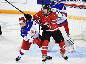 Canada's Jennifer Wakefield gets her stick up as she battles with Russia's Anna Shibanova (left) in front of Russia's net during their Tuesday game at the women's world hockey championships in Kamloops.