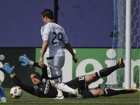 New York City FC goalkeeper Josh Saunders dives to block a shot attempt by Vancouver Whitecaps forward Octavio Rivero in NYC's 3-2 victory at Yankee Stadium in the Bronx Saturday.