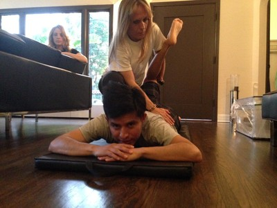 Jockey Mario Gutierrez works on stretching with fitness coach Sabrina Perruzi as his wife Rebecca looks on in their home. He's now in the top 10 in U.S. jockey rankings.