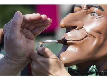 A joint is lit at a vendor's display at the annual 4:20 marijuana event at it's new location, Sunset Beach, Vancouver April 20 2016.