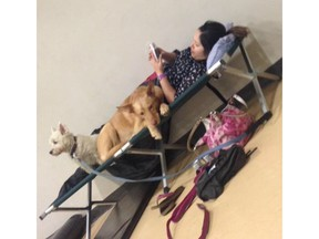 Former Kelowna resident who lives in Fort McMurray, Alta., Holly Hashimi resting on a cot with her dogs at an evacuation centre in Albion, Alta. Hashimi and her husband had to evacuate their home in the Abasand neighbourhood, which they believe has burned down.