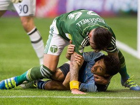 Vancouver Whitecaps' Nicolas Mezquida is taken to the ground by Portland Timbers' Liam Ridgewell during the first half of Saturday's game at B.C. Place.