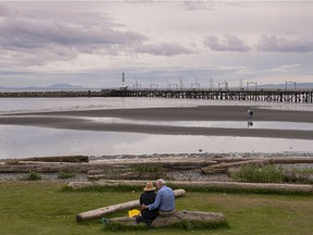 A couple enjoys a moment on a quiet day in White Rock on Wednesday. Following the recent condo fire in the city, renewed talk of amalgamation with Surrey has started. Richard Lam/PNG
