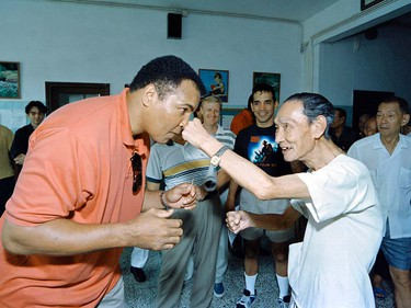 """(FILES) This file photo taken on September 01, 1994 shows Boxing great Muhammad Ali receiving a punch from a 79 old """"sparring-partner"""" during a visit in a old people's home in Macau. Boxing legend Muhammad Ali, dies at 74. The former heavyweight world champion was hospitalized on Thursday at a Phoenix, Arizona, hospital with a respiratory issue, which US media reported was complicated by his Parkinson's disease.  / AFP PHOTO / Mike FialaMIKE FIALA/AFP/Getty Images"""