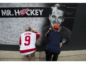 People sign a memorial wall as thousands of people line up to pay their respects to NHL Hall-of-Famer Gordie Howe as the casket rests in the Joe Louis Arena in Detroit, Mich., on Tuesday, June 14, 2016.