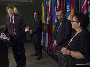 Vancouver Mayor Gregor Robertson gestures to Chief Maureen Thomas of the Tsleil-Waututh Nation as Chief Ian Campbell (centre-left) of the Squamish Nation and hereditary Chief and councillor Howard Grant (centre-right) on behalf of the Musqueam Nation look on during a news conference on Parliament Hill in Ottawa on Tuesday.