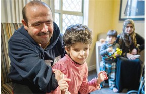 Mohamad El Refaie, left and his wife Shamia El Refaie, right, tend to their blind seven-year-old daughter Heba, centre left and Lema, 4, centre right at a hotel in Surrey.