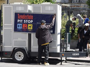 John Leggett helps to install portable toilets in the Tenderloin district of San Francisco on June 28. The Tenderloin district is commonly known as a hotbed for homelessness where people often relieve themselves on the streets. Vancouver Coun. Andrea Reimer on Monday met with housing advocates and lawyers in San Francisco to look at innovative ways to reign in uncooperative landlords who specialize in low-income housing. — Getty Images files