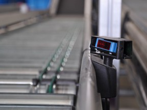 A roller conveyor with a laser distance sensor on the side. Smaller and faster sensors, tied to more powerful computers, are revolutionizing industrial processes.