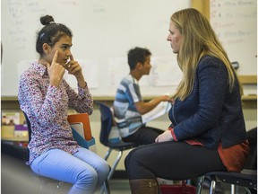 Jin Yusuf, 13, from Syria talks with Daniela Olmunger, one of six delegates from Sweden who talked with refugee students attending Charles Tupper Secondary in Vancouver, Oct. 5, 2016. (Arlen Redekop / PNG photo)