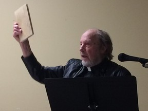 Fr. Charles Brandt, who supports himself as a hermit by restoring ancient books and manuscripts, holds up an antiquarian collection of the teachings of the Desert Fathers, the first Christian hermits from 1,600 years ago.