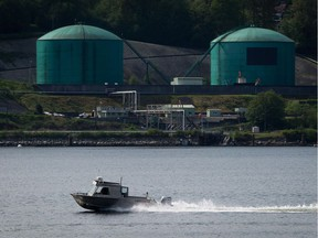 A fishing boat in North Vancouver passes Kinder Morgan's Westridge Marine Terminal in Burnaby, on the shores of Burrard Inlet. This would be the terminus of the Trans Mountain pipeline.