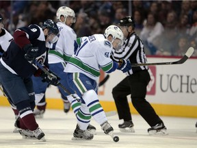 Troy Stecher kicks the puck away from Colorado Avalanche centre Matt Duchene on Saturday, when the Vancouver Canucks rookie defenceman played 24:30 in Denver.