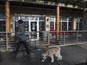 A woman walks past the Rose and Crown Pub where police found a 53-year-old man unconscious.