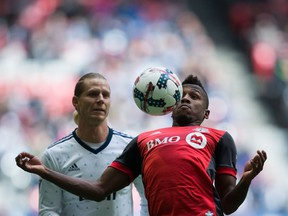Toronto FC midfielder Armando Cooper, right, knocks the ball down in front of Whitecaps midfielder Brek Shea during the first half of an MLS game in Vancouver on Saturday.
