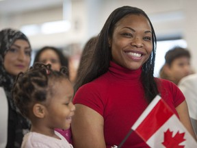 Thirty new Canadians took their oath of citizenship at the Immigrant Services Society of B.C. Welcome Centre in Vancouver on Wednesday. Pictured is Messia Ditshimba, originally from Congo, and daughter Akira being greeted by Ahmed Hussen, federal minister of immigration.