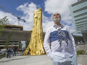 Artist Douglas Coupland with his sculpture The Golden Tree.