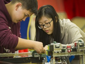 Matthias Bernhard and Denise Chan work on a robot at Gladstone Secondary School in Vancouver on Tuesday. A team from the school is going to the robotic world championships in Louisville, Ky., later this month.