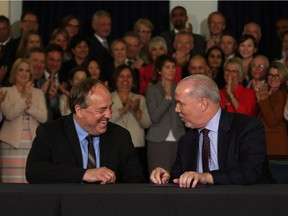 B.C. NDP leader John Horgan and B.C. Green party leader Andrew Weaver signed an agreement on creating a stable minority government during a press conference in the Hall of Honour at Legislature in Victoria, B.C., on Tuesday, May 30, 2017.