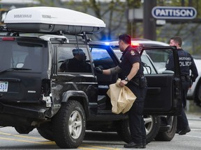A VPD officer bags items from a black Jeep SUV boxed in by several police vehicles at E6th Ave. in Vancouver on May 2, 2017.