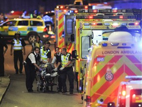 Police officers and members of the emergency services attend to a person injured in an apparent terror attack on London Bridge in central London on June 3, 2017. Armed police fired shots after reports of stabbings and a van hitting pedestrians on London Bridge on Saturday in an incident reminiscent of a terror attack in March just days ahead of a general election.