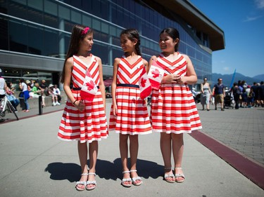From left to right, ten-year-old triplets, Elizabeth Ferguson, Danielle Ferguson and Chloe Ferguson, who were born in the United Arab Emirates, pose for a photograph after receiving their Canadian citizenship during a special Canada Day ceremony in Vancouver, B.C., on Saturday July 1, 2017. THE CANADIAN PRESS/Darryl Dyck