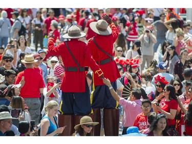 Stilt walkers dressed as Mounties walk among the crowd at the Canada Day celebrations at Canada Place, Vancouver, July 01 2017.