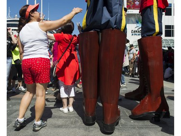 A woman reaches for a stilt walker dressed as a Mountiesin the crowd at the Canada Day celebrations at Canada Place, Vancouver, July 01 2017.