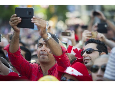 A man records the crowd singing O Canada at the Canada Day celebrations at Canada Place, Vancouver, July 01 2017.