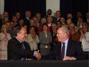 B.C. NDP leader John Horgan and B.C. Green party leader Andrew Weaver shake hands after signing an agreement on creating a stable minority government during a press conference in the Hall of Honour at Legislature in Victoria on May 30, 2017.