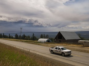 An RCMP officer drives north on Highway 97S near Alexandria, B.C., while a large plume of smoke from the forest fires burning around Williams Lake can be seen on the horizon, July, 16, 2017.